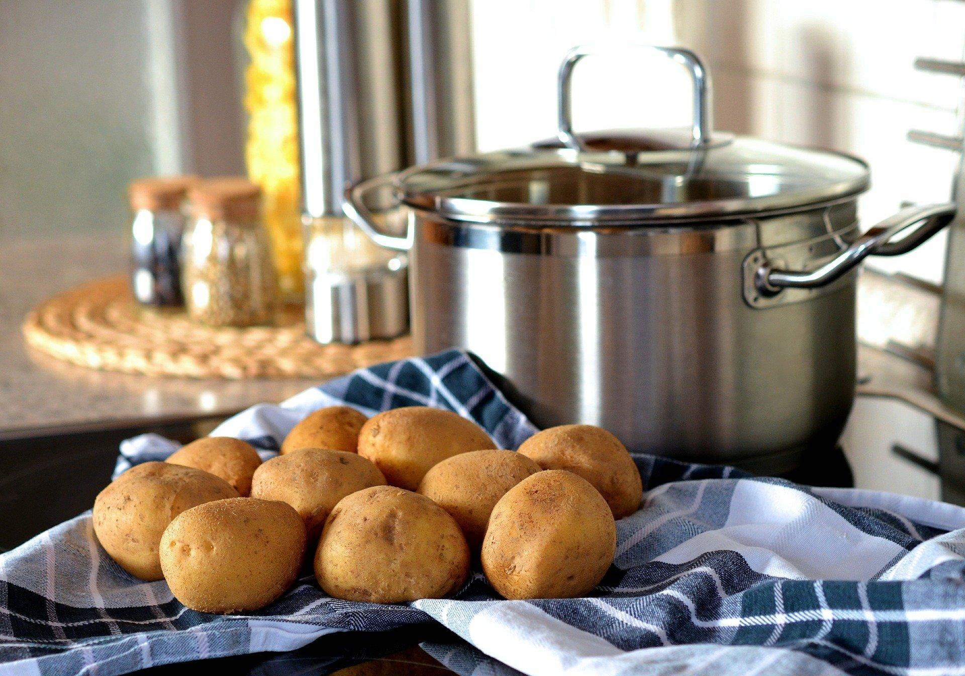 Caçarola de inox ao fundo com prato de batatas a frente