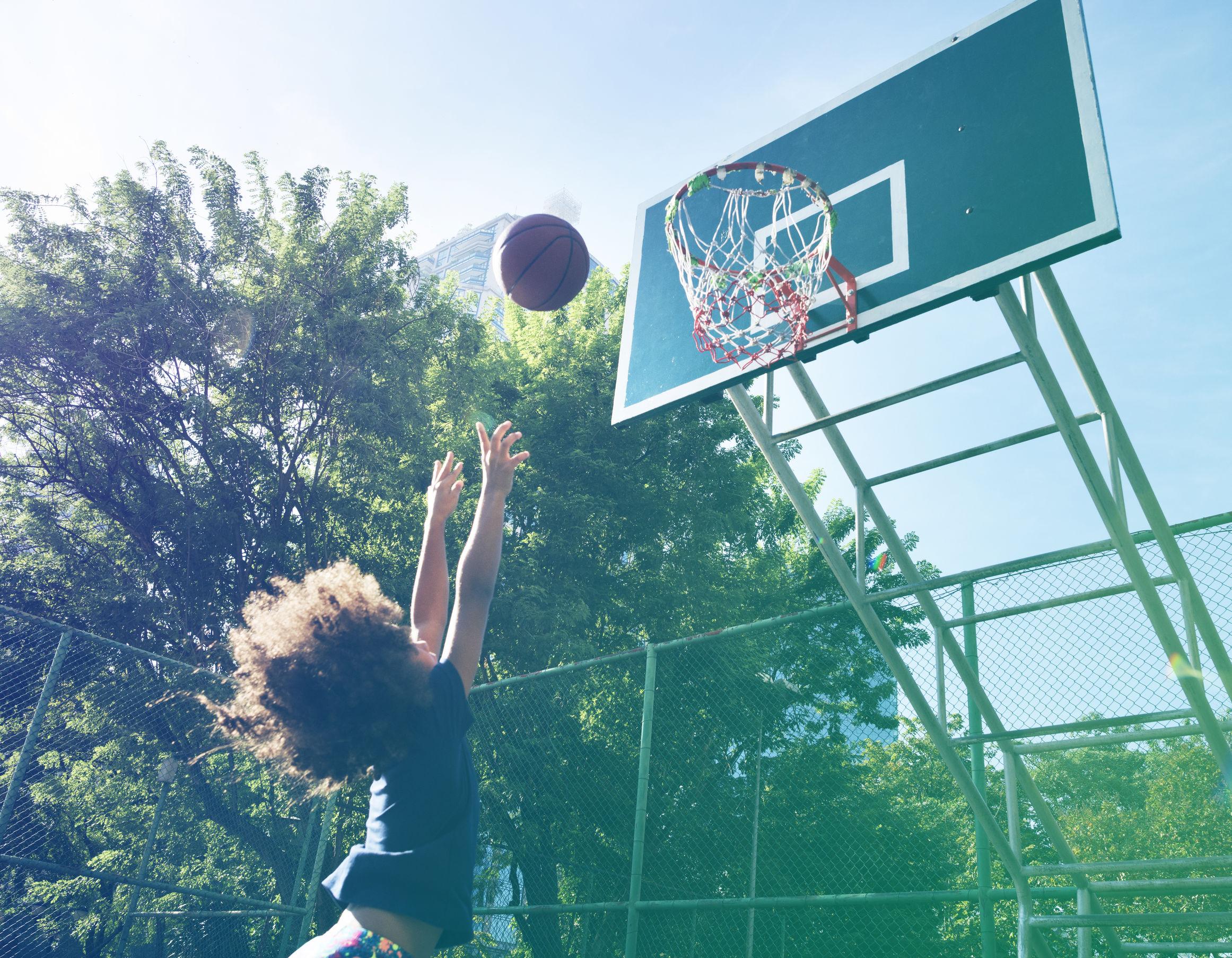 Na foto um menino tentando acertar uma bola em uma cesta de basquete.