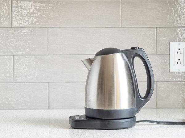 Foto de chaleira elétrica em inox apoiada sobre a bancada da cozinha