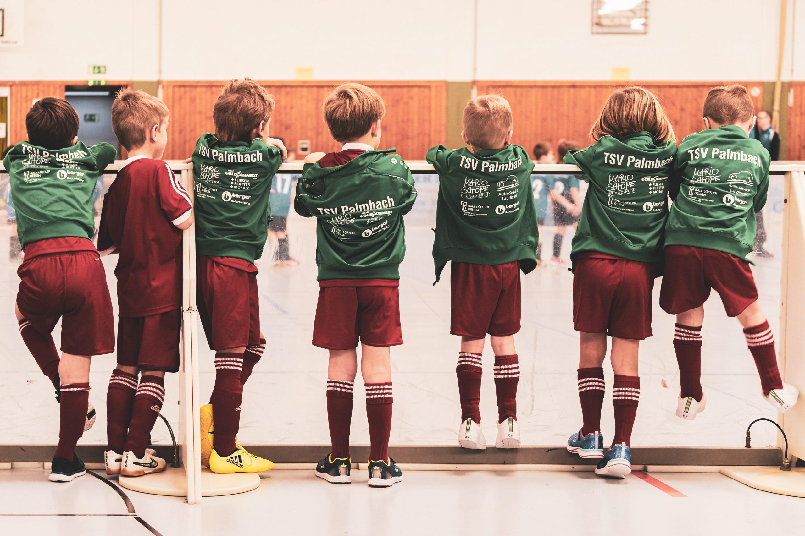Imagem mostra sete crianças com o uniforme de um time infantil, todas com chuteiras de futsal e alinhadas atrás da proteção de acrílico de uma quadra, observando um jogo que lá se desenrola.