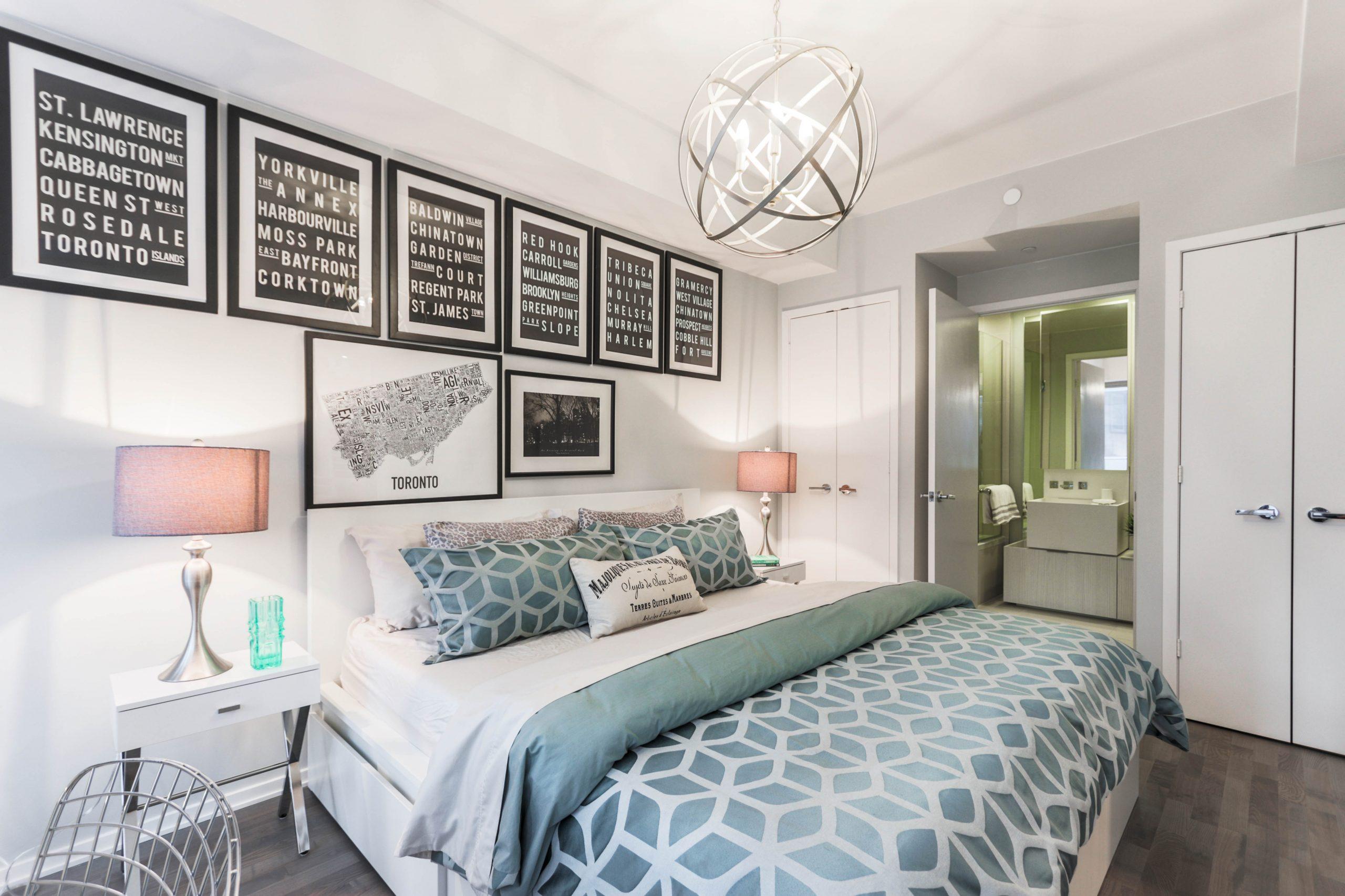 Na foto um quarto de casal com quadros na parede, abajures, roupa de cama verde e piso de madeira.