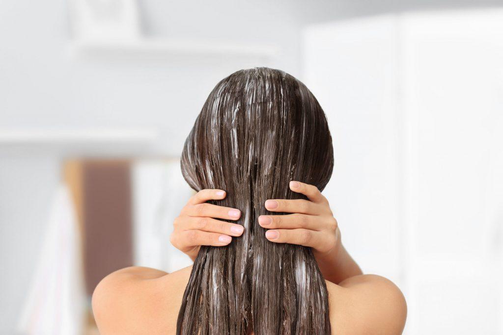 Na foto uma mulher de costas com creme nos cabelos e a mão sobre eles.
