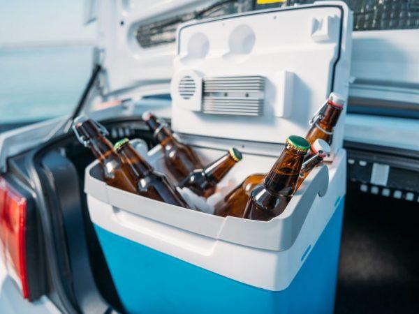 Na foto um cooler azul dentro do porta malas de um carro.