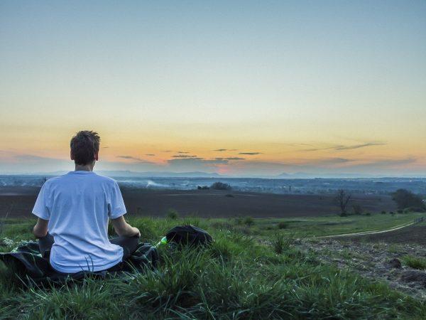 Homem sentado na grama, meditando.