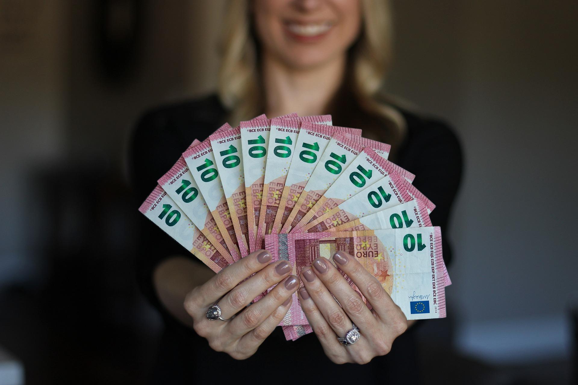 Mulher mostrando notas de dinheiro.