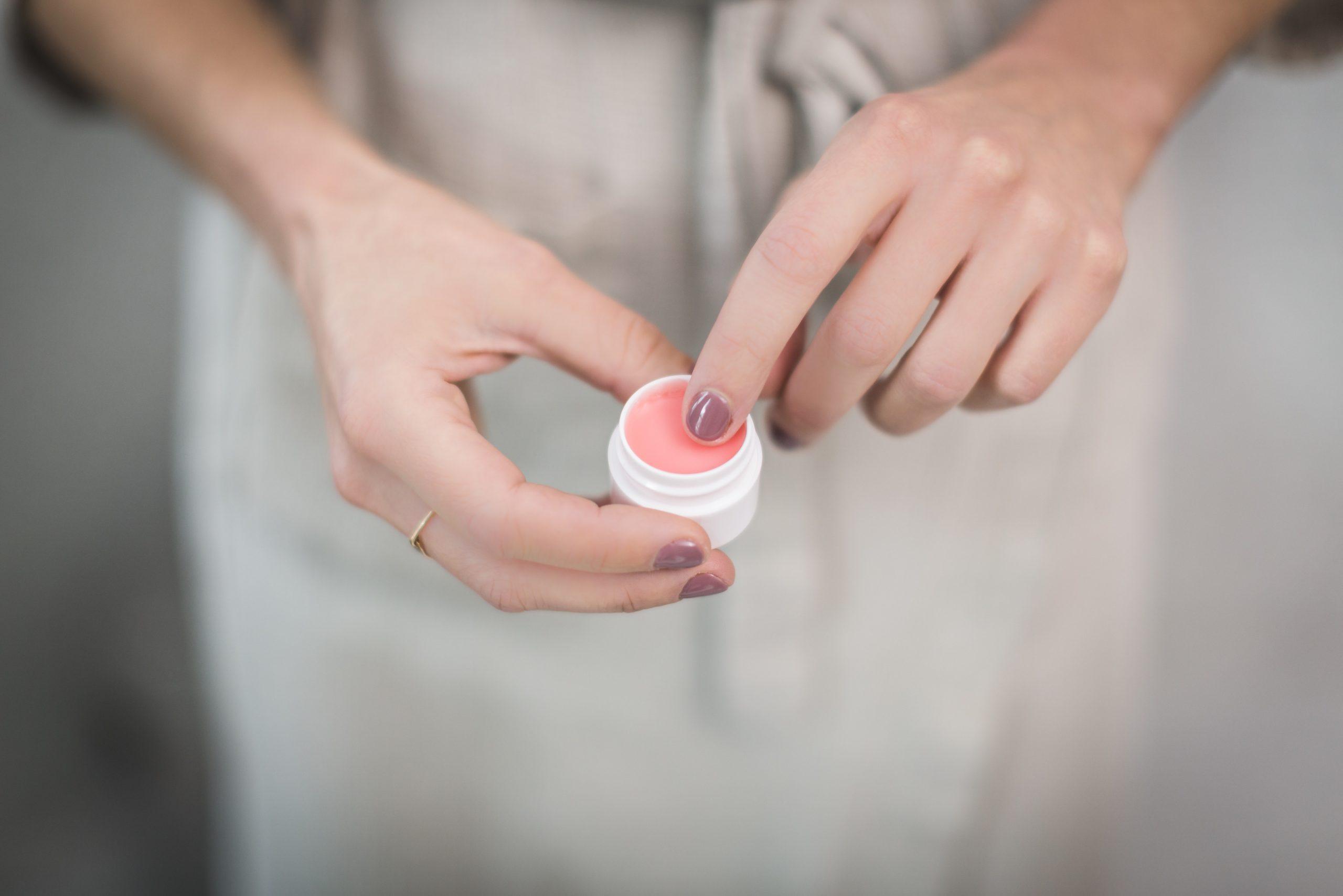 Foto que mostra duas mãos femininas segurando um pequeno potinho do que parece ser um esfoliante labial. Um dos dedos toca diretamente o produto, como se fosse aplica-lo.