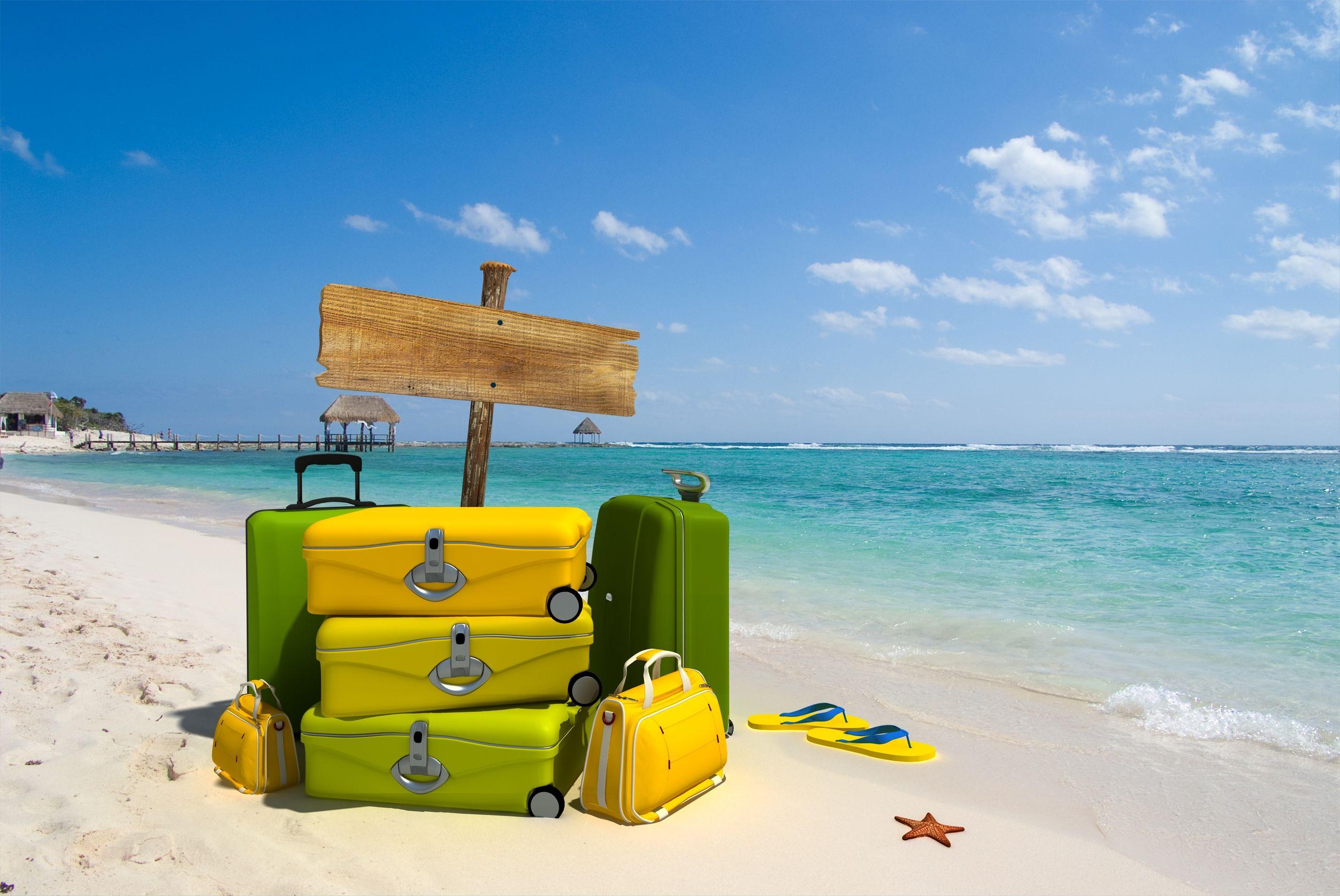 Na foto diversas malas juntas em uma praia.
