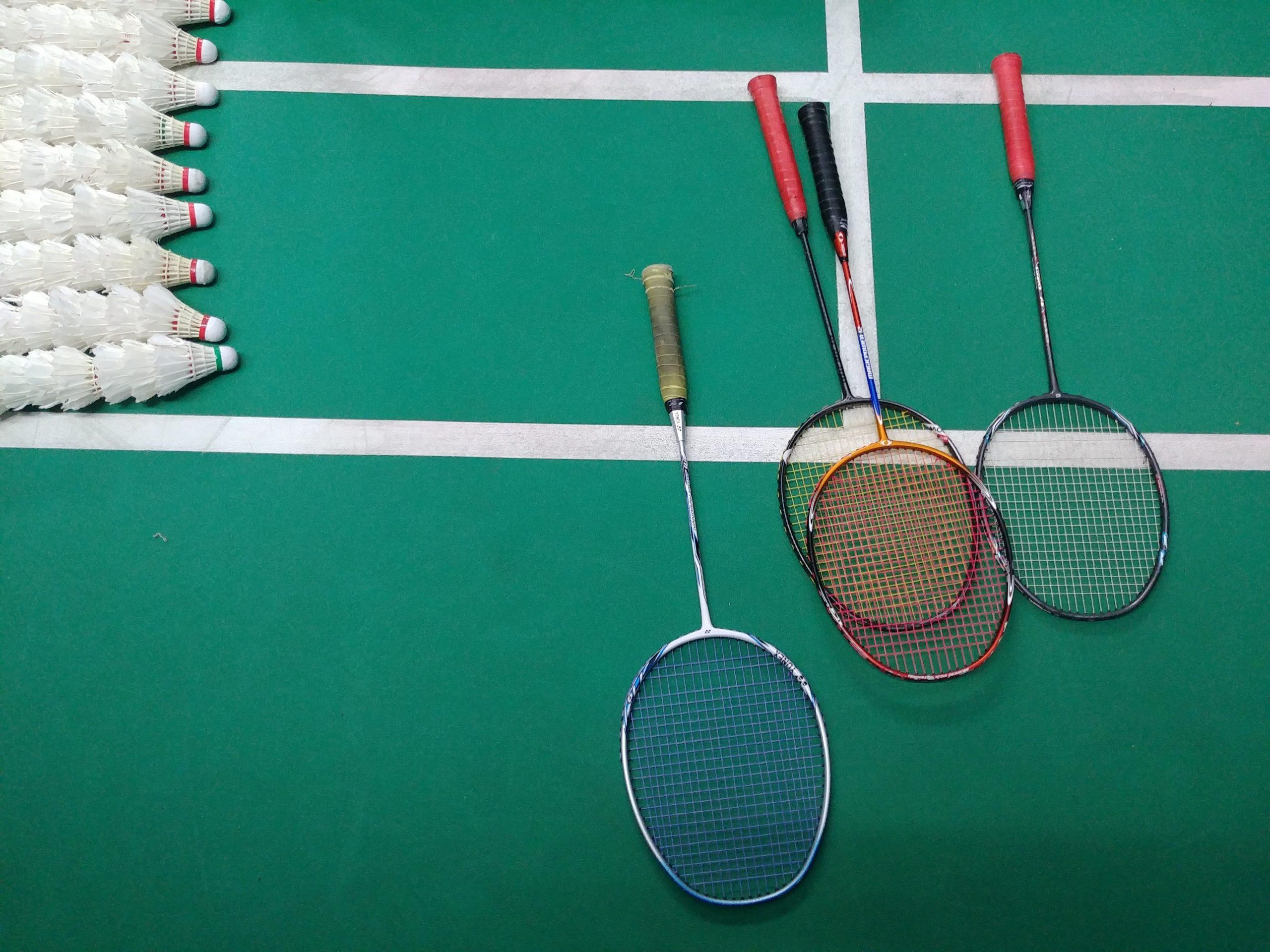 Imagem mostra uma composição, com quatro raquetes deitadas sobre as linhas de uma quadra de badminton. Ao seu lado, quase saindo do quadro, nove fileiras de petecas.