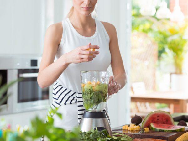 Moça preparando suco verde em liquidificador apoiado na bancsda da cozinha
