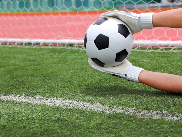 Imagem mostra o close das mãos de um goleiro, usando luvas, defendendo uma bola, mas já atrás da linha do gol.