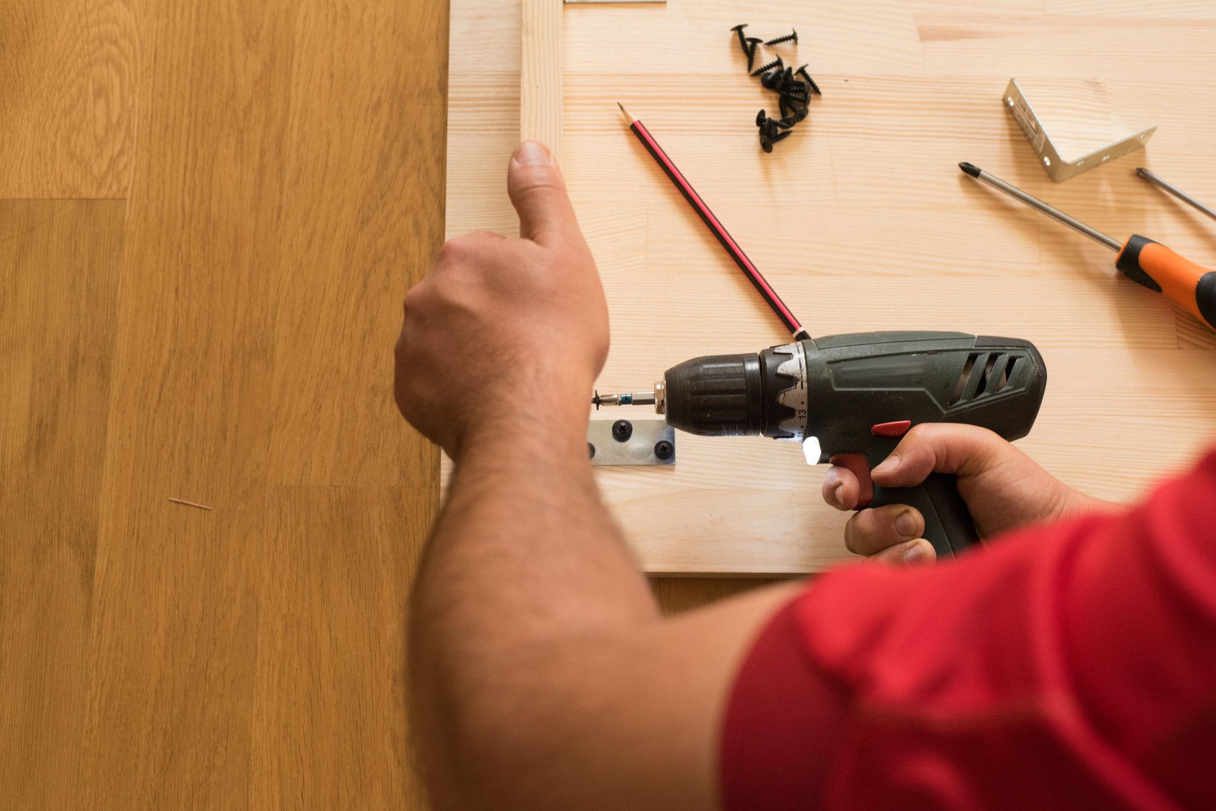 Imagem mostra uma pessoa usando uma parafusadeira em uma madeira.