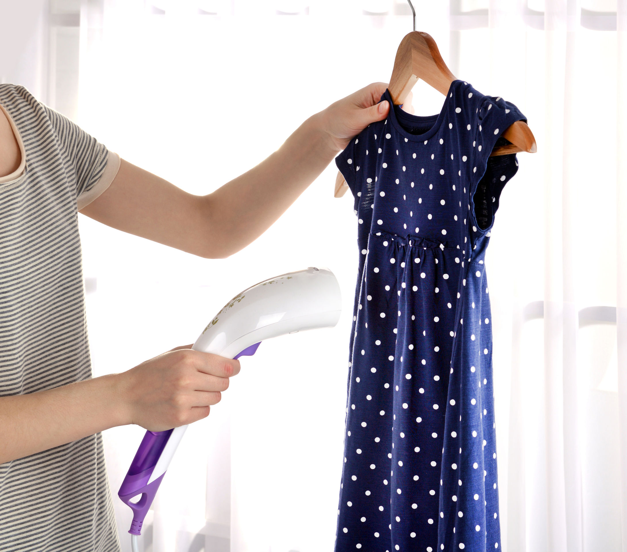 mulher passando roupa no quarto