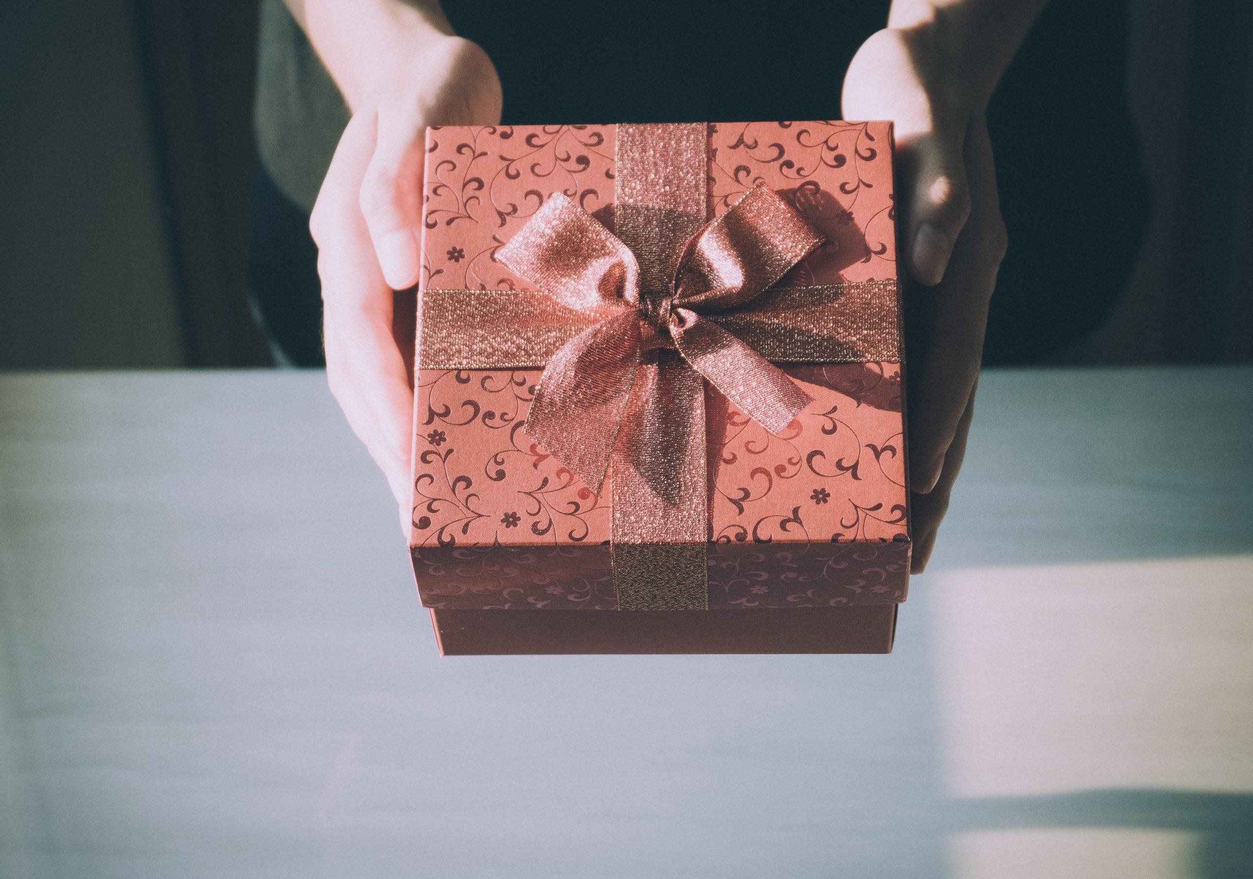 Na foto uma pessoa segurando um presente.