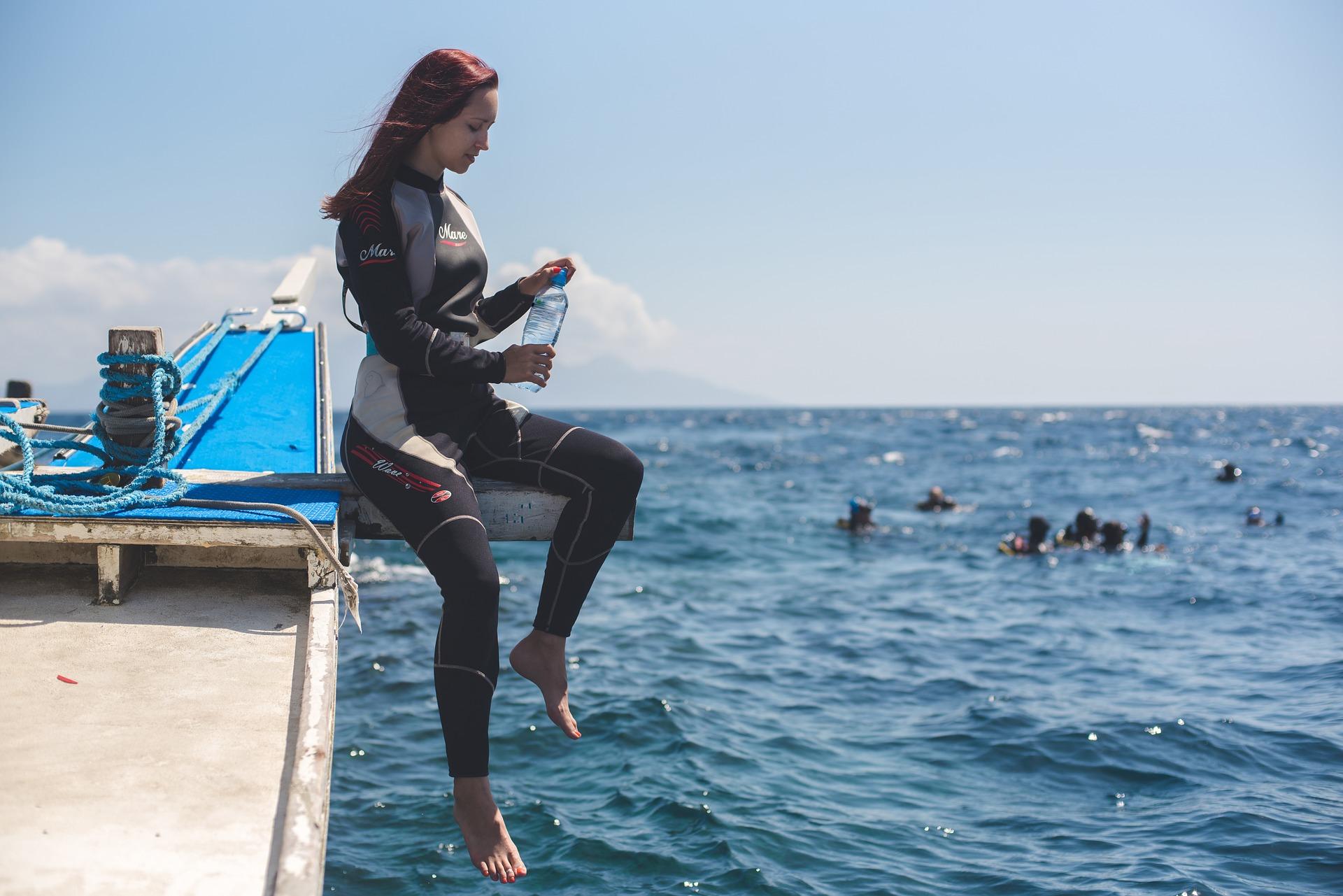 Imagem mostra uma mulher, usando roupa de mergulho, sentada no deck de um barco sobre o mar. Ao fundo, é possível enxergar um grupo de mergulhadores na superfície da água.