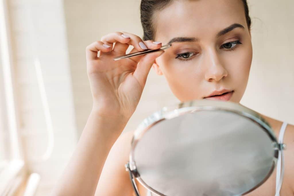 Na foto uma mulher segurando uma pinça em frente a um espelho.