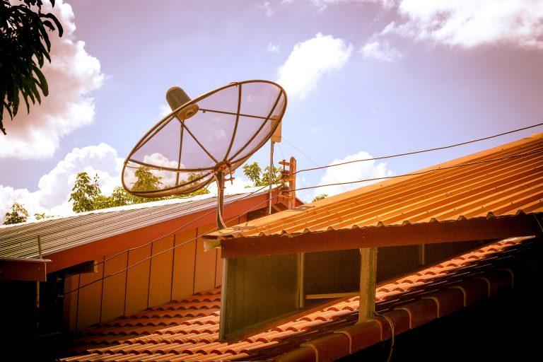 Imagem de uma antena parabólica em cima de um telhado