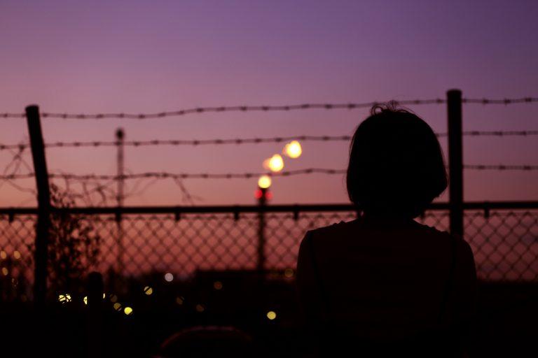 Imagem mostra uma silhueta feminina obervando uma cerca de arame farpado em uma cidade.