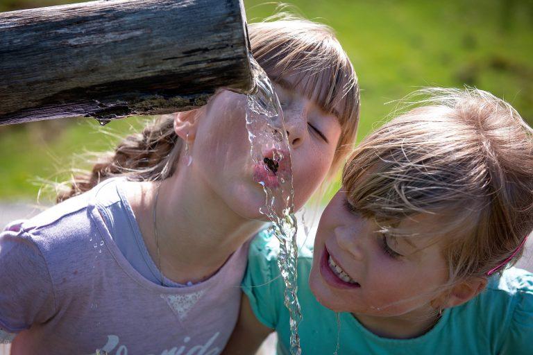 Imagem mostra duas meninas bebendo água diretamente de um cano.