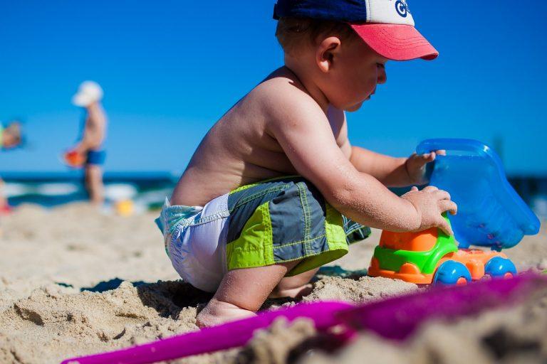 Imagem de menino brincando com caminhão de plástico na areia