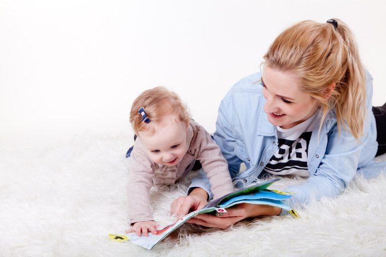 Na foto uma bebê e uma mulher deitadas em um tapete olhando para um livro de tecido.