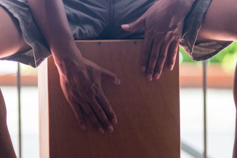 foto em close das mãos de um homem que está sentado no instrumento tocando cajon