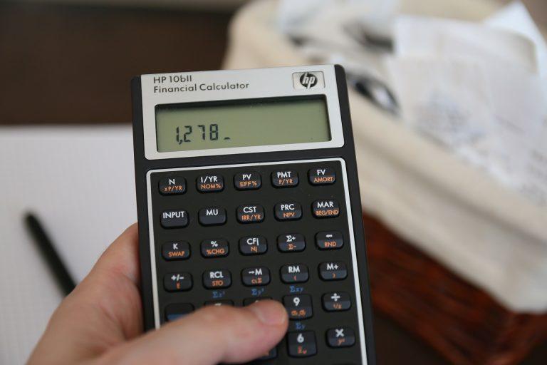 Mãos manipulam calculadora financeira HP