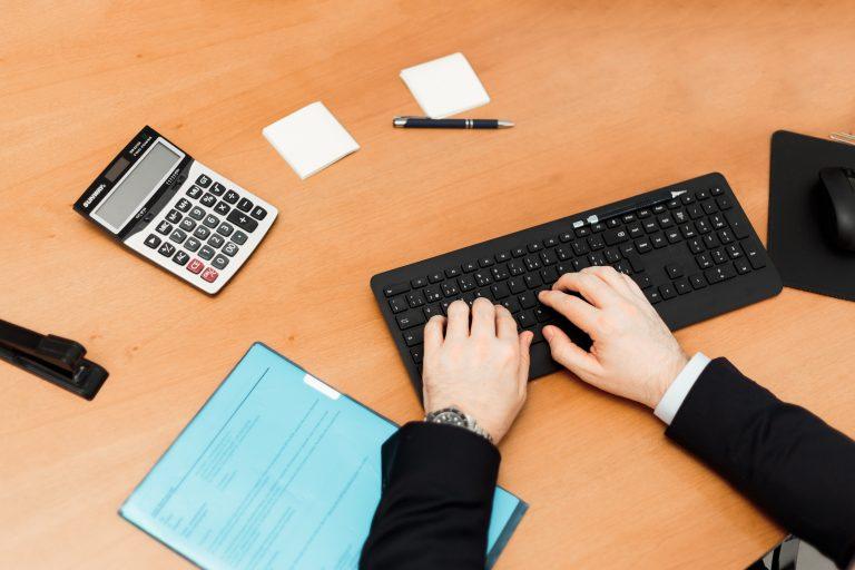 Homem digitando em teclado de computador, com calculadora de mesa ao lado.