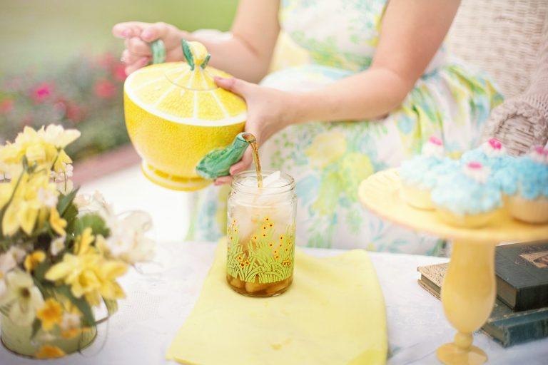 Mulher servindo chá com uma chaleira decorativa.