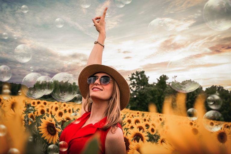 Na foto uma mulher de roupa vermelha, chapéu e óculos de sol no meio de uma plantação de girassóis.