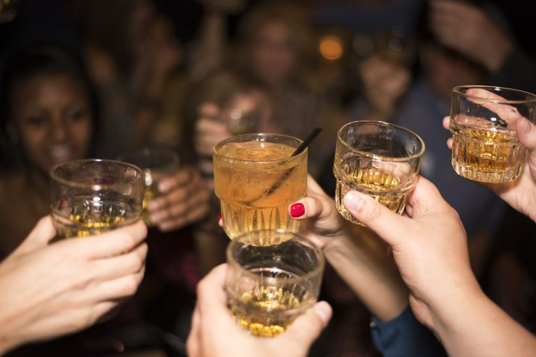 Imagem mostra um grupo de pessoas fazendo um brinde com copos cheios de whisky.