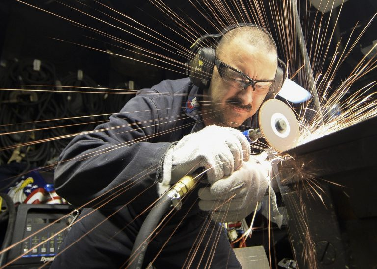 Imagem mostra um homem cortando metais com óculos, protetor auricular, luvas e demais equipamentos de proteção.