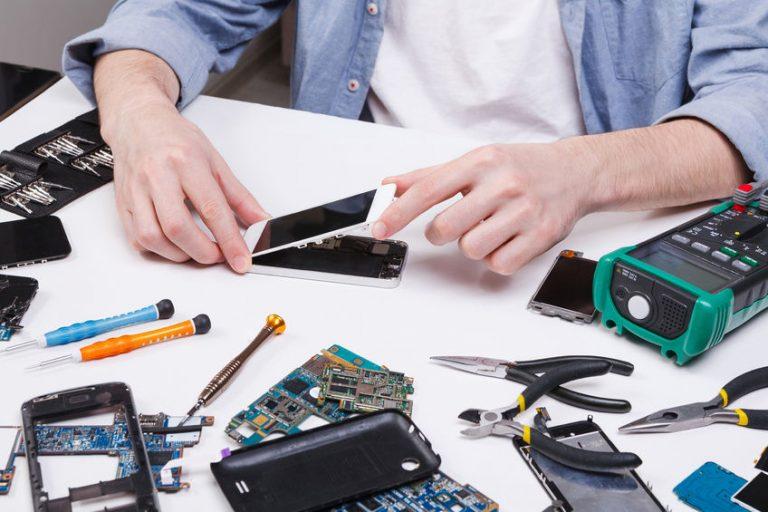 Imagem mostra uma pessoa consertando um celular com diversas ferramentas e peças espalhadas sob a mesa