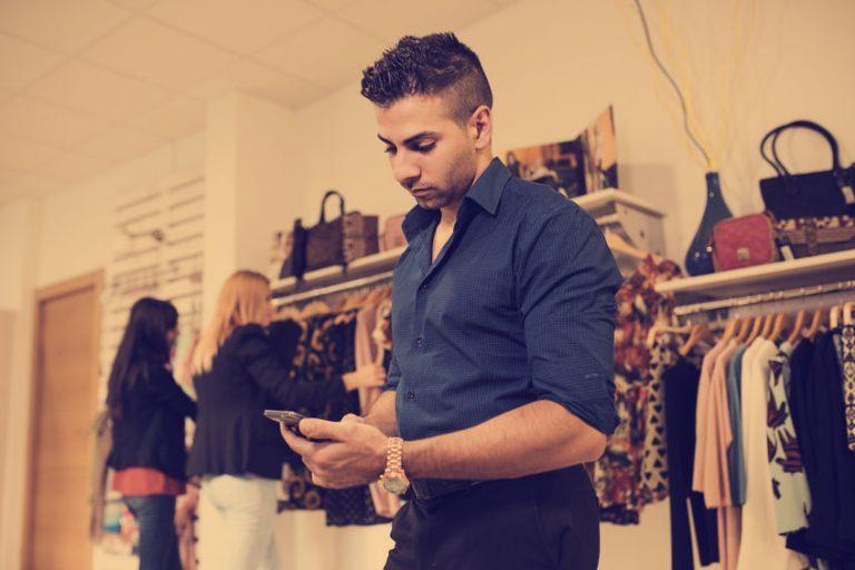 Rapaz mexe em celular enquanto usa fone de ouvido Motorola
