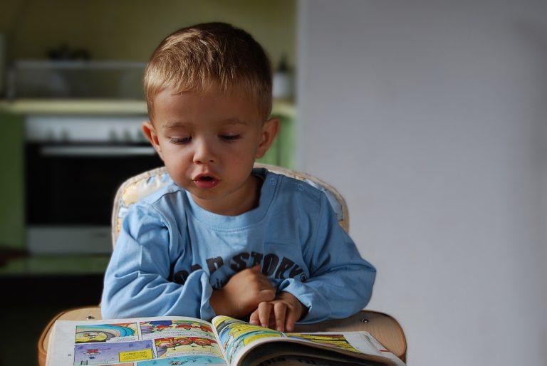 Menino pequeno sentado em um cadeirão lendo um gibi
