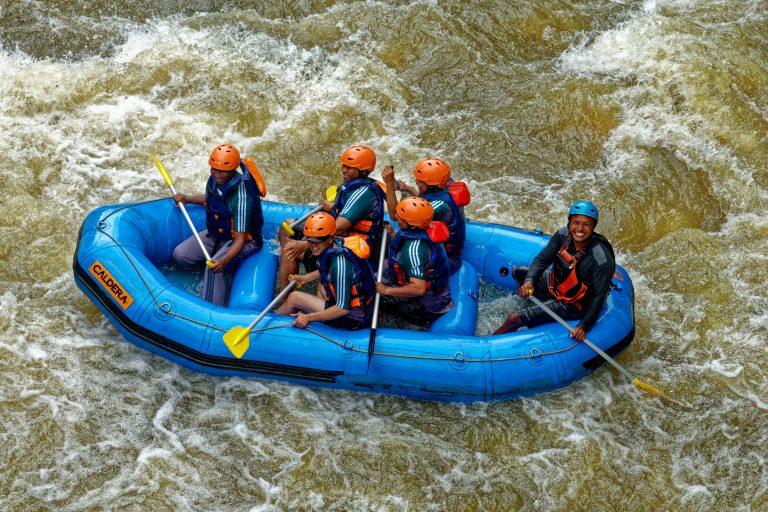 Imagem mostra um grupo de seis pessoas fazendo rafting com um bote inflável.