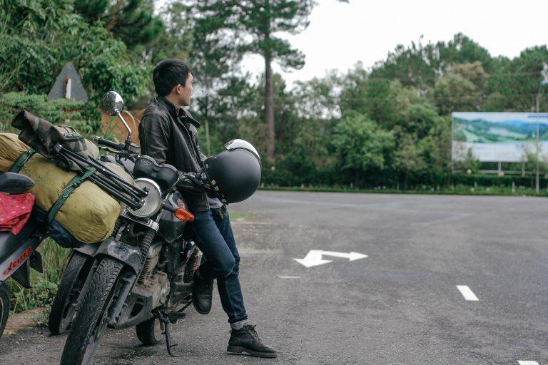 Imagem mostra um homem parado ao lado de uma moticicleta e vestindo uma jaqueta de motoqueiro.