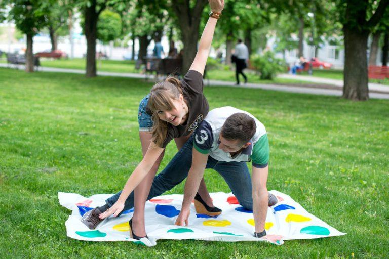 Imagem mostra um rapaz e uma moça jogando twister num parque, com braços e pernas entrelaçados sobre o tapete de bolinhas.