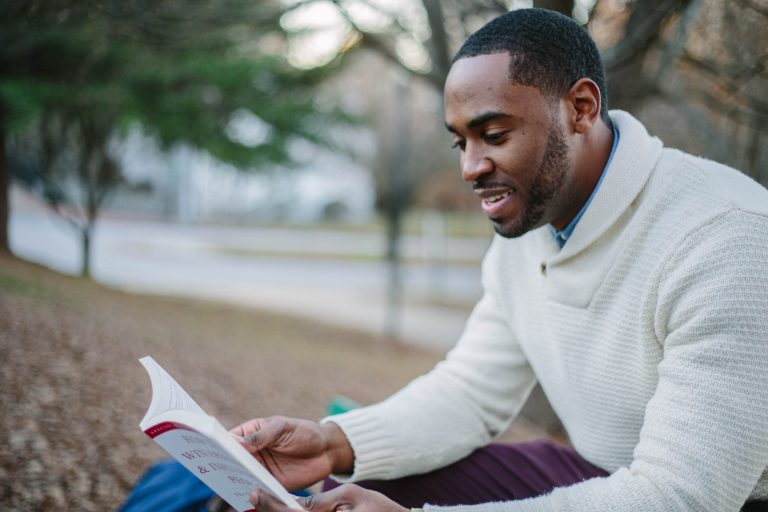 Imagem mostra um homem sorrindo enquanto lê um livro, sentado num parque.