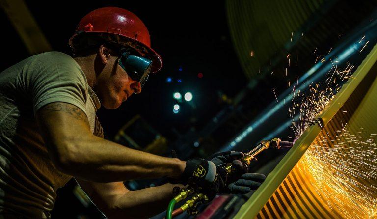 Imagem mostra um homem com capacete e viseira fazendo uso de um maçarico no trabalho.