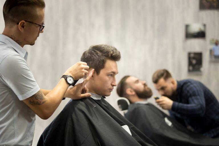 Imagem com um homem em pé cortando o cabelo de um homem que está sentado, ao fundo outro homem em pé fazendo a barba de um homem sentado.