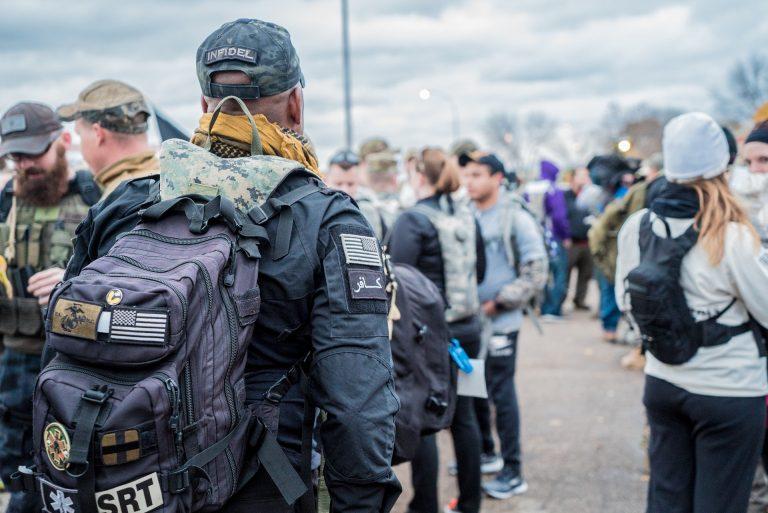 Imagem mostra um homem de costas com mochila militar em meio a uma multidão