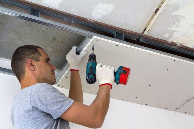 Imagem mostra um homem usando uma furadeira no teto.