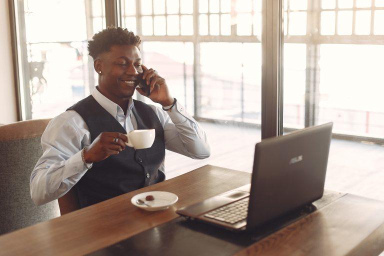 Homem tomando café com notebook à frente.
