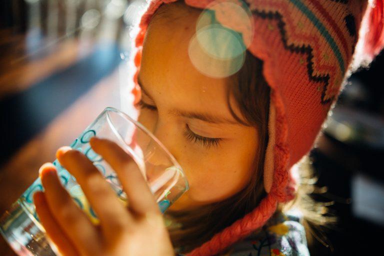 Imagem mostra uma criança bebendo em um copo de vidro, que segura com a mão direita.