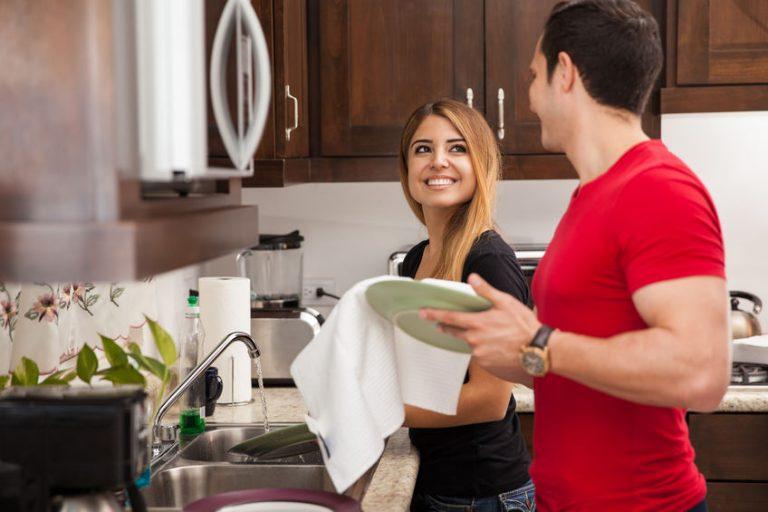 Casal troca sorrisos enquanto ela lava e ele enxuga a louça