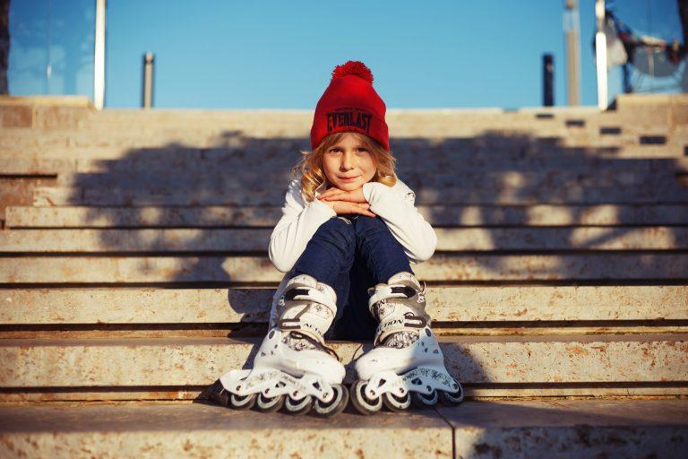 Criança sentada em escada usando patins.