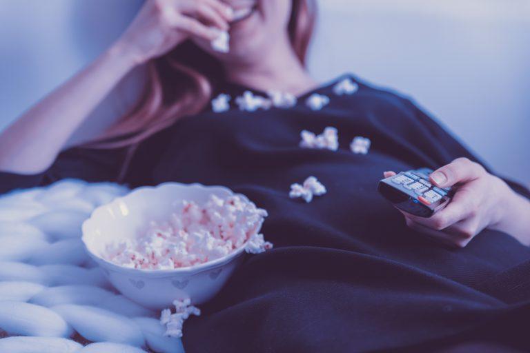 Na foto uma mulher deitada segurando um controle remoto com um balde de pipoca do lado.
