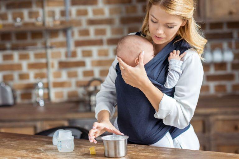 Mãe prepara mamadeira enquanto segura bebê em sling