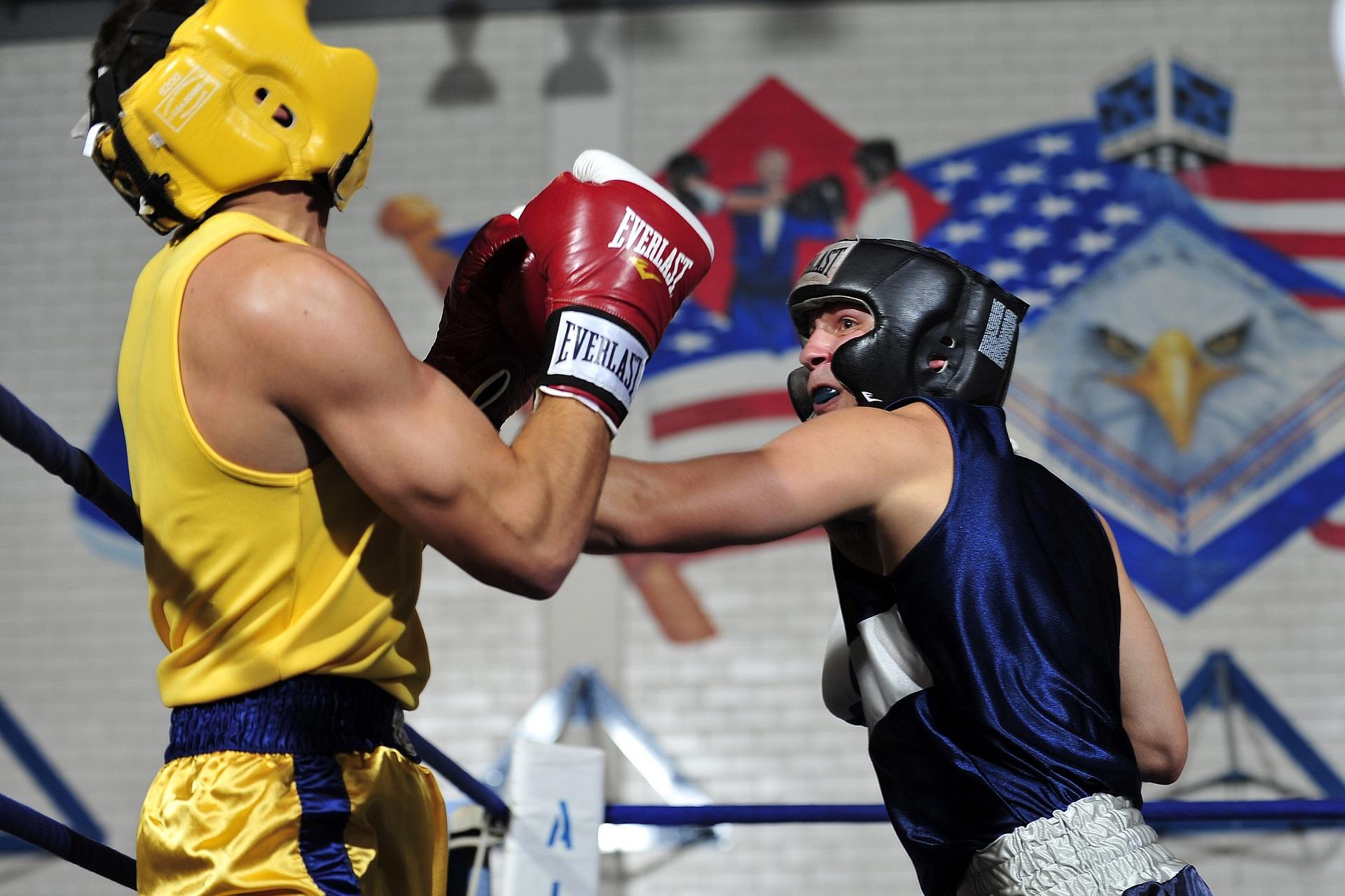 Imagem mostra dois homens lutando boxe.