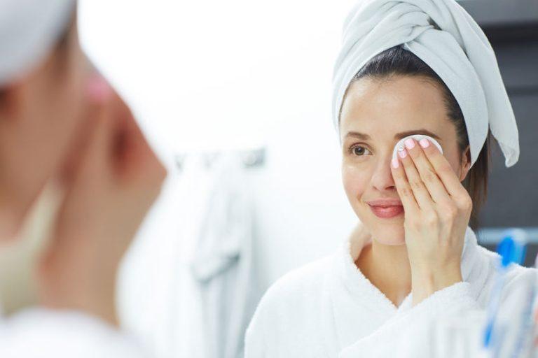 Foto de uma mulher de roupão e toalha no cabelo, se olhando no espelho com leve sorriso no rosto e aplicando produto de beleza na região dos olhos, com um algodão.